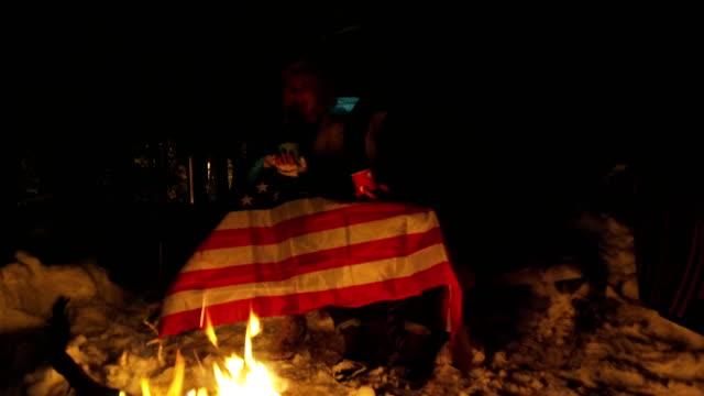 Cute couple drinking tea near camp fire
