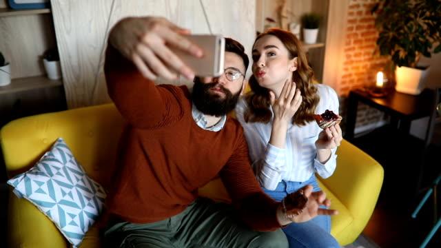 vídeos de stock, filmes e b-roll de belo casal comendo e tomando selfie no seu sofá - fofo descrição geral
