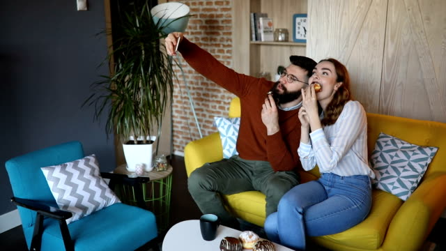 cute couple eating and taking selfie on their sofa - doughnut stock videos & royalty-free footage
