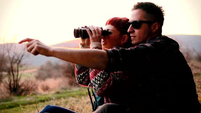 vídeos de stock e filmes b-roll de casal fofinho divirta-se através de uma caminhada de piquenique - observar pássaros