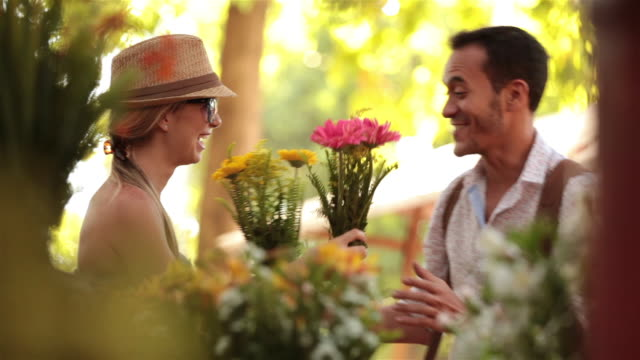 Cute couple in Brazilian marketplace smell colorful flowers and laugh together
