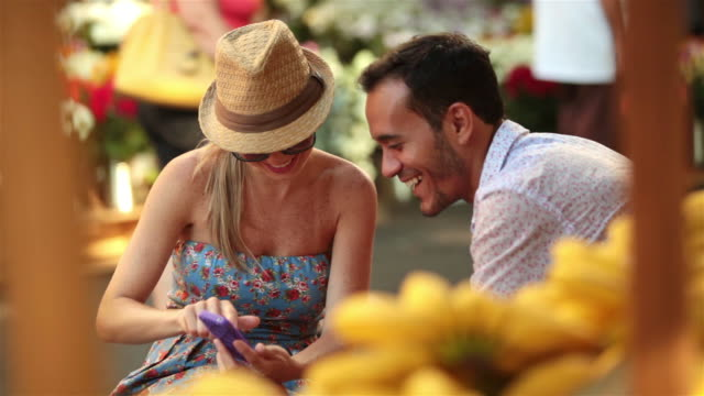 cute couple look at smartphone and chat in busy brazilian marketplace - boyfriend stock videos & royalty-free footage