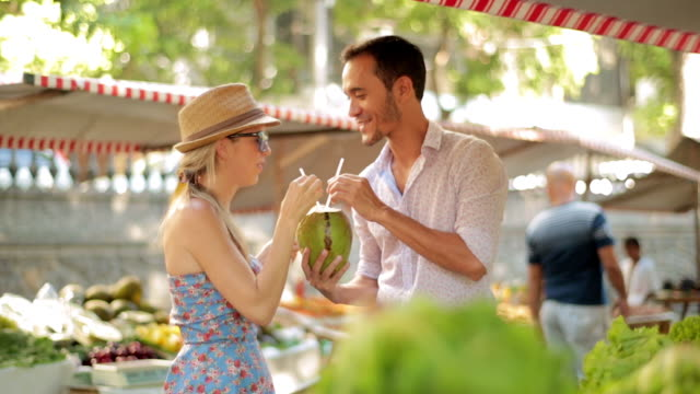 cute couple share coconut water in sunny brazilian marketplace - coconut stock videos & royalty-free footage