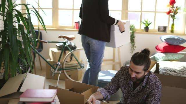 cute couple sitting in new home around unpacked boxes - tenant stock videos & royalty-free footage