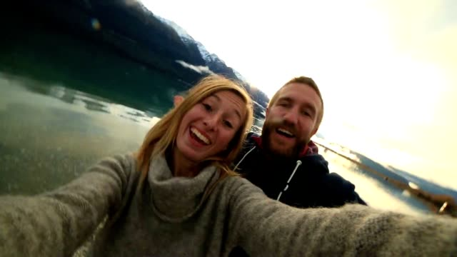Cute couple take selfie by the lake at sunset