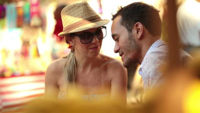 vidéos et rushes de cute couple talk and study smartphone in busy brazilian marketplace - chapeau