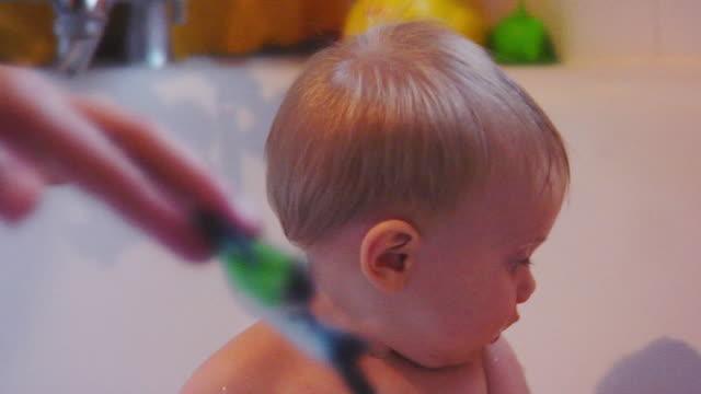 vídeos de stock e filmes b-roll de cute, curious baby boy reaching for toy in bathtub - menino infancia pelado banheiro