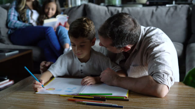 cute dad and son drawing together on foreground while mom is reading a book with daughter at background - figlio maschio video stock e b–roll