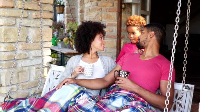 vidéos et rushes de fille et parents mignons détendant sur une balançoire de porche - loggia