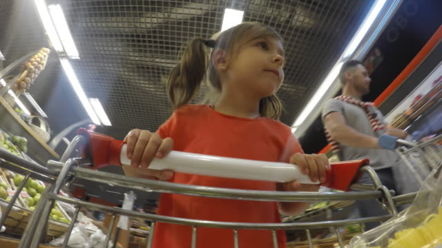 pov cute daughter doing grocery shopping with father - trolley stock videos and b-roll footage