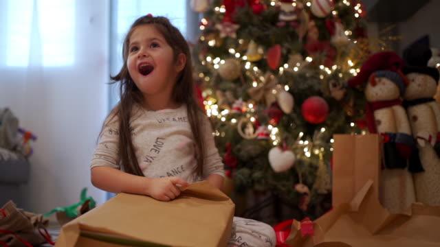 nettes ekstatisches kind überrascht mit einem geschenk unter einem weihnachtsbaum - weihnachtsmann stock-videos und b-roll-filmmaterial