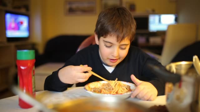 cute elementary age boy eating spaghetti for dinner in dinning room - ketchup stock videos and b-roll footage