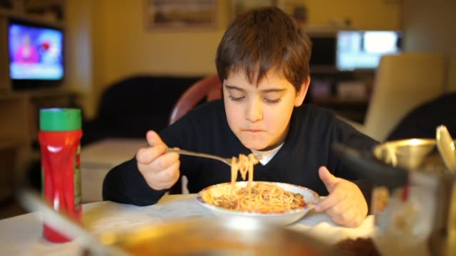 cute elementary age boy eating spaghetti for dinner in dinning room - spaghetti stock videos & royalty-free footage