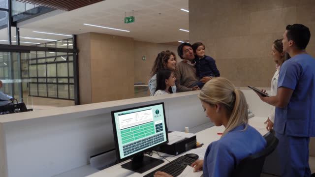 cute family of four walking into the hospital for a paediatrics consult arriving to the reception and nurse hading them a form - scrubs stock videos & royalty-free footage