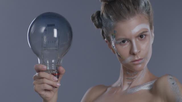 söt modell i scenen make-up bakom bubblor, hålla glödlampa. fashion video. - ängel bildbanksvideor och videomaterial från bakom kulisserna