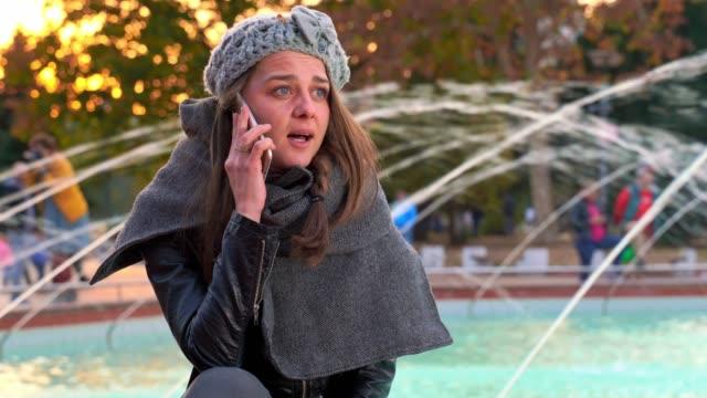 Cute fashionable girl sitting near fountain talking on phone