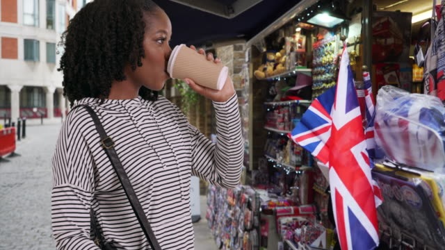 cute female drinks coffee and looks at souvenirs at shopping stall in london - souvenir stock videos & royalty-free footage