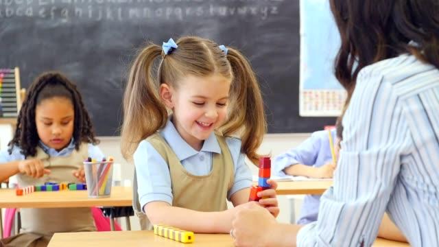 vídeos de stock e filmes b-roll de cute female preschool student enjoys using counting blocks at school - criança em idade escolar
