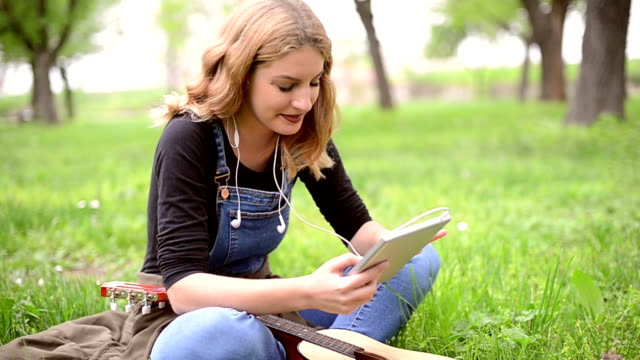 cute female sitting in the park and using touch pad - electronic book stock videos & royalty-free footage