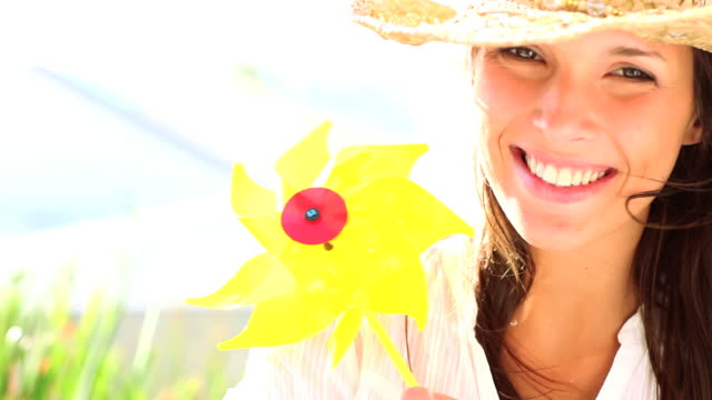 cute female wearing a sun hat and playing with pinwheel - sun hat stock videos & royalty-free footage