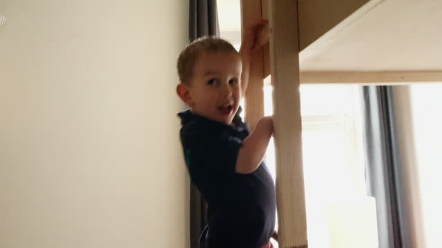 a cute, five year-old caucasian boy runs into his room, climbs the wooden ladder of his bunkbed, and lays down on his pillow in his bedroom - ladder stock videos & royalty-free footage