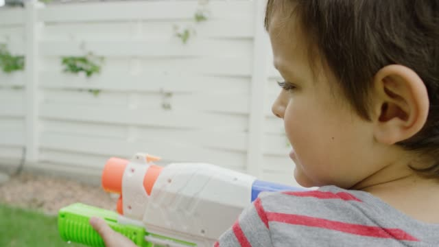 a cute five year-old caucasian boy shoots water from his toy water gun in a green backyard with trees and grass - toy gun stock videos & royalty-free footage
