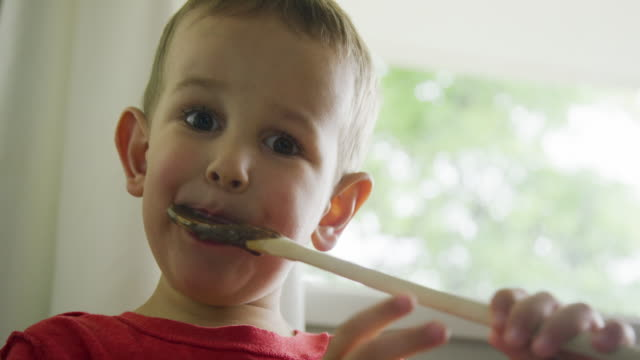 a cute four year-old caucasian boy licks chocolate cake batter from a wooden spoon contentedly in a kitchen - memories stock videos & royalty-free footage