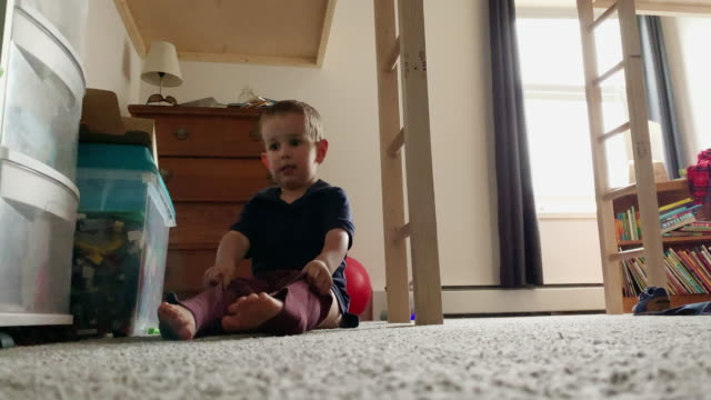 a cute, four year-old caucasian boy sitting on the floor of his bedroom pulls on his pants and stands up - trousers stock videos & royalty-free footage