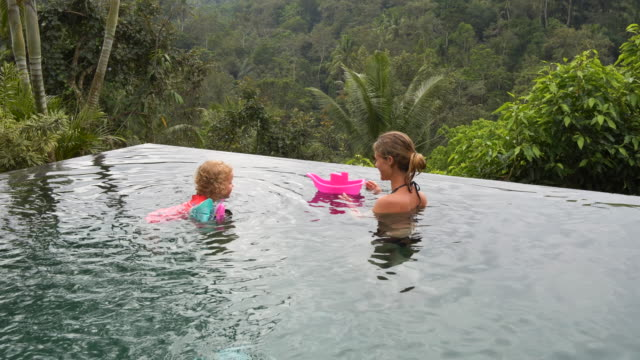 cute girl and mother playing at infinity pool - ubud stock videos & royalty-free footage