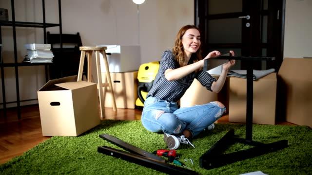 vídeos de stock e filmes b-roll de cute girl assembling stuff at home - apartamento