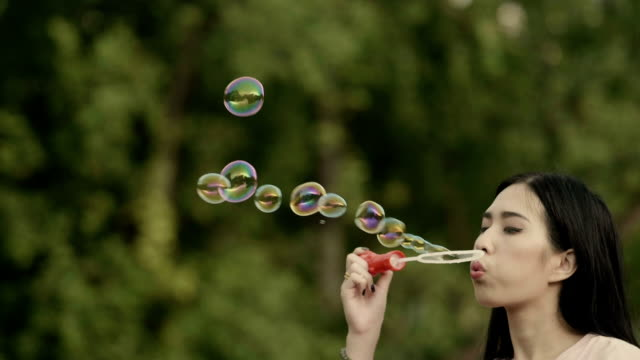 cute girl blowing soap bubbles at the park - bubble wand stock videos & royalty-free footage