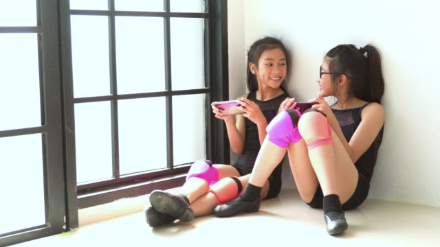 stockvideo's en b-roll-footage met schattig meisje danser en partner het nemen van een pauze door het spelen van een smartphone - 8 9 jaar