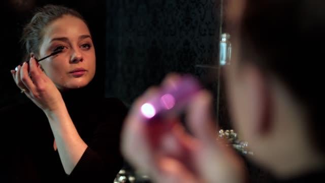 Cute girl doing her make up applying mascara and looking at camera smiling