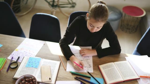 自宅で一人で宿題をするかわいい女の子 - 学校備品点の映像素材/bロール