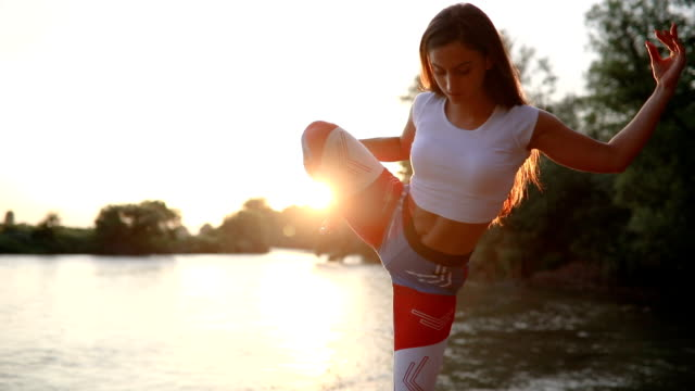 Cute girl doing yoga by the river