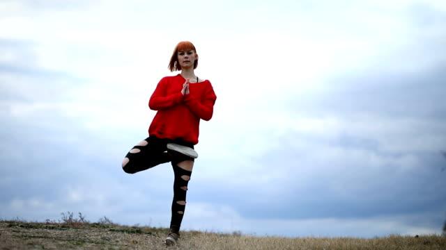 vídeos de stock, filmes e b-roll de menina bonito que faz a ioga no parque público - pose de arvore
