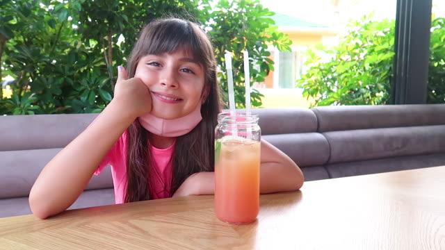 vidéos et rushes de cocktail mignon de boisson de fille avec le masque - seulement des petites filles