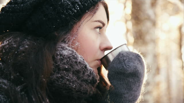 cute girl drinking hot drink in the forest - warm clothing stock videos and b-roll footage