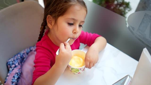 vídeos y material grabado en eventos de stock de linda chica comiendo helado mirando dibujos animados - helado de vainilla