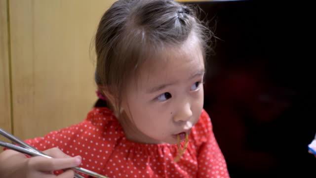cute girl eating tokpokki traditional korean food - bacchette cinesi video stock e b–roll