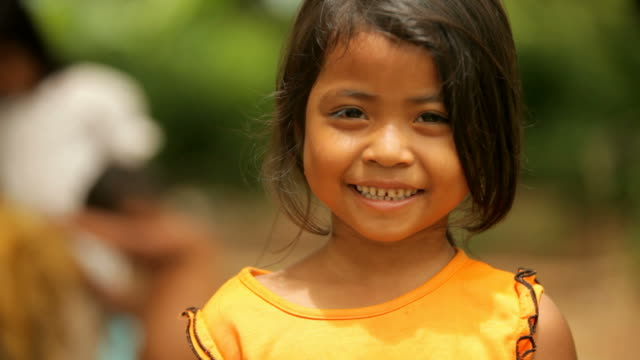 ragazza carina sorridente in cambogia - povertà video stock e b–roll