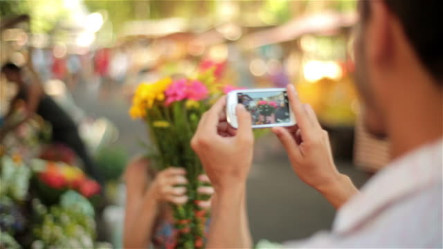 cute girl hides face behind bouquet of flowers and peeks out for smartphone photo in sunny marketplace - florist stock videos & royalty-free footage