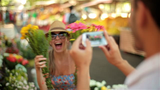 vidéos et rushes de cute girl hides face behind bouquet of flowers and peeks out for smartphone photo in sunny marketplace - cache