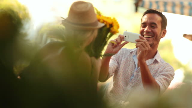 vídeos de stock e filmes b-roll de cute girl hides face behind bouquet of flowers and peeks out for smartphone photo in sunny marketplace - fotografar