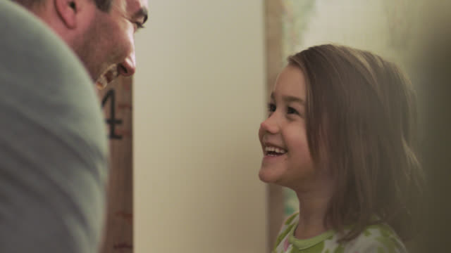 cu. cute girl in pajamas points at height on bedroom wall in amazement and dad gives her goodnight kiss. - messen stock-videos und b-roll-filmmaterial