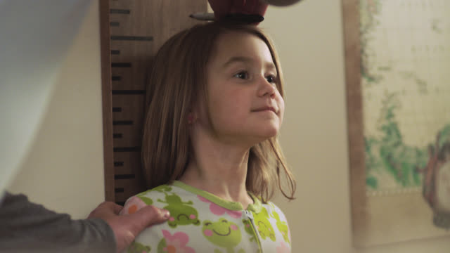 cu. cute girl in pajamas stands still while father measures her height against bedroom wall with a marker. - measuring stock videos & royalty-free footage