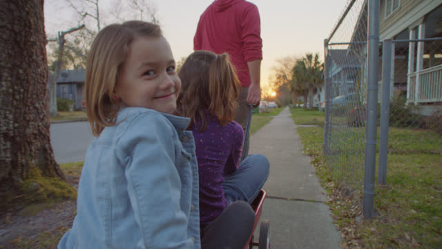 MS SLO MO. Cute girl in red wagon turns and smiles at camera on neighborhood sidewalk.