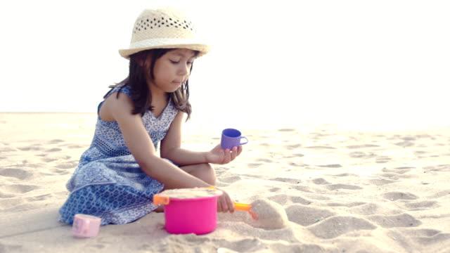 かわいい女の子はプレイをビーチで楽しみます。 - 帽子点の映像素材/bロール