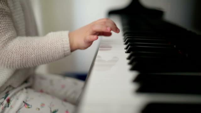 vídeos de stock e filmes b-roll de fofinho menina aprendendo a tocar piano - tecla de piano