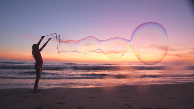 cute girl making giant bubbles on the beach - bubble wand stock videos & royalty-free footage